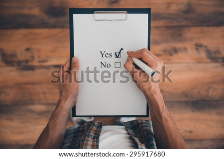 Making a right choice. Top view of man making a check mark in clipboard while standing on the wooden floor  - stock photo