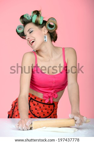 Making a surprise for him. Sexy young housewife kneading the dough on the table - stock photo