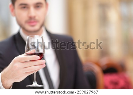 Making a toast. Handsome young man in suit raising his glass of wine while making a toast in luxury restaurant with selective focus