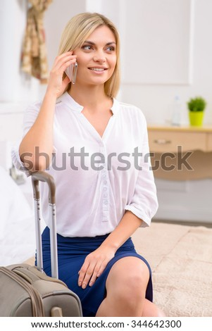 Making arrangements. Attractive young woman sitting at the edge of bed in her hotel room and busy making calls. - stock photo