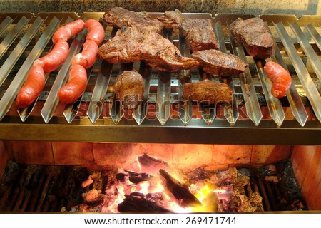 Making barbecue  Steak and sausage over high heat. - stock photo