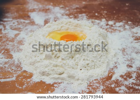 Making bread, mixing food ingredients: egg yolk on a flour staple closeup. Retro colors. Grain added - stock photo
