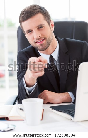 Making business easier. Confident young man in formal wear pointing you and smiling while sitting at his working place