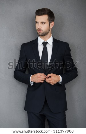 Making business looking good. Confident young businessman adjusting his jacket and looking away while standing against grey background - stock photo