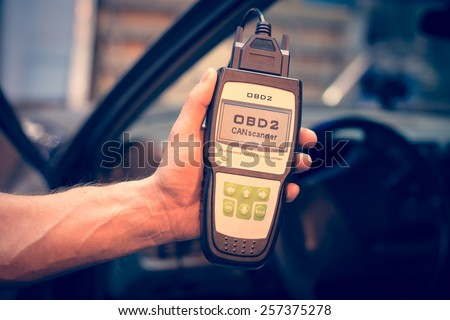 Making car diagnostics using obd device. OBD is On Board Diagnostics, an electronics self diagnostic system, typically used in automotive applications - stock photo