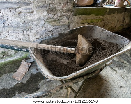Making cement in a wheelbarrow,small scale diy construction. With shovel.