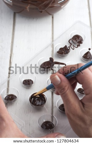 Making chocolate candies in mold - stock photo