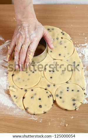 Making Chocolate Chip Cookies. Series. Using cookie cutters to cut out rounds. - stock photo