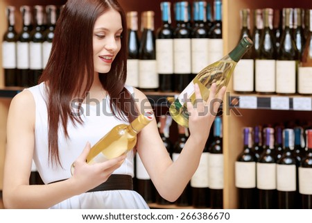 Making choice. Young smiling woman with expression of hesitation comparing two bottles of wine in a liquor store - stock photo