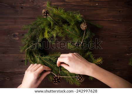 Making Christmas wreath with hands on brown wooden background - stock photo