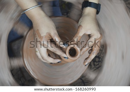 Making clay pot with hands shaping up the pot while the wheel is spinning  - stock photo