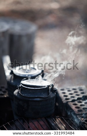 Making coffee by the campfire in forest - stock photo