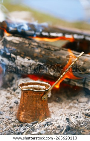 Making coffee in the fireplace  on camping or hiking in the nature - stock photo