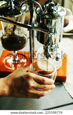making coffee with hand and a cup of coffee making coffee with Belgian Royal style Syphon or siphone Coffee Maker Machine