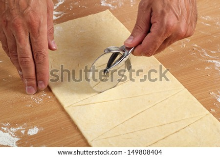 Making Croissant Cookies with Jam. Series. Cutting dough with cutter into triangles. - stock photo