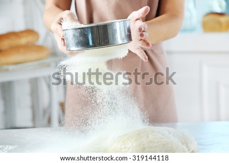 Making dough by female hands at bakery - stock photo
