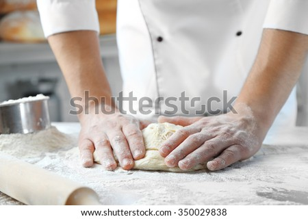 Making dough by male hands at bakery - stock photo
