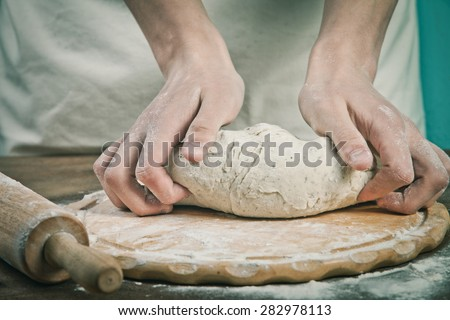 Making dough by mens hands on wooden table background