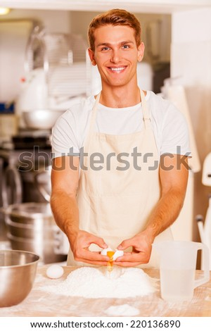 Making dough for pastry. Confident young male baker cracking egg while holding it upon flour  - stock photo
