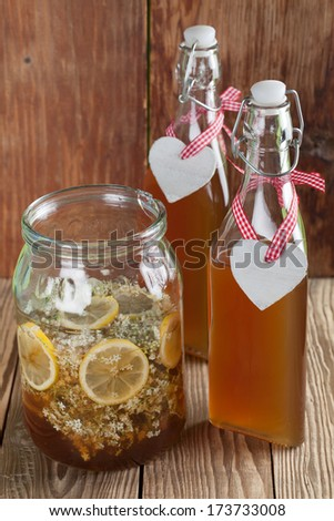 Making elderberry syrup with lemons and cane sugar, alternative medicine for cough, cold or flu. - stock photo