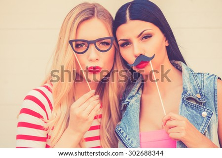 Making funny faces. Two playful young women making faces while standing outdoors