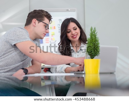 Making great decisions. Young people staring a new business and discussing something with their colleagues at office table - stock photo