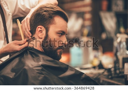 Making hair look magical. Close-up side view of young bearded man getting haircut with straight edge razor by hairdresser at barbershop - stock photo