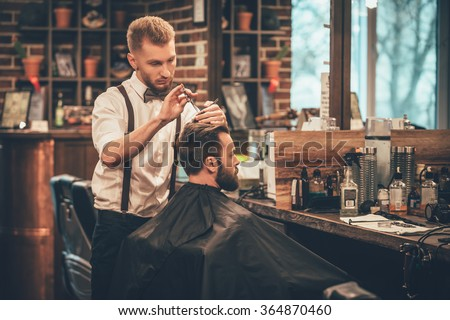 Making hair look magical. Young bearded man getting haircut by hairdresser while sitting in chair at barbershop - stock photo