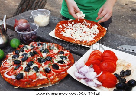 making hand made pizza with olives and tomatoes on wooden table on picnic - stock photo