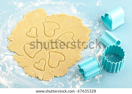 Making heart shaped shortbread cookies with cutters, dough