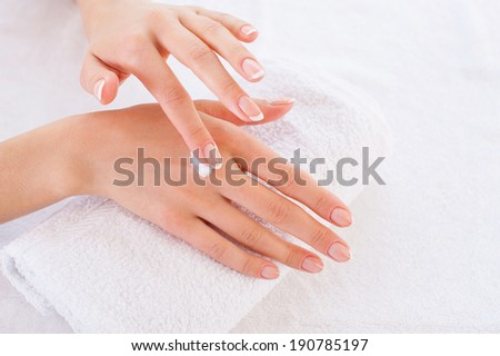 Making her skin clean and smooth. Close-up of woman applying cream on hand