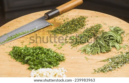 Making herb butter/array of chopped herbs on cutting board