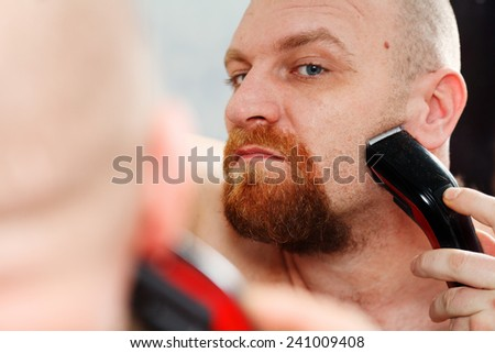 Making his beard perfect. Confident young bearded man shaving with electric razor  - stock photo