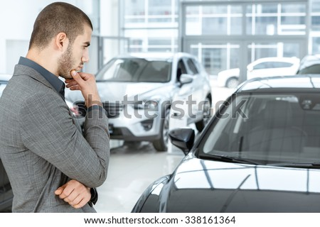 Making his choice. Horizontal portrait of a young man in a suit looking at the car and thinking if he should buy it - stock photo