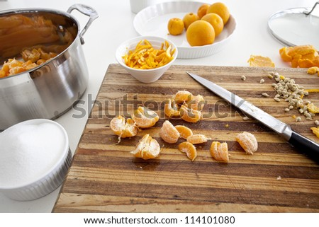 Making mandarin jam on white workbench with wooden chopping board - stock photo