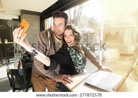 Making memories. Beautiful heterosexual couple taking selfie and having a good time in a local coffee shop. - stock photo