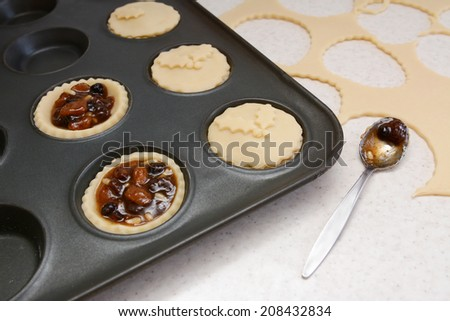 Making mince pies, with rolled out pastry scraps and teaspoon of mincemeat - stock photo