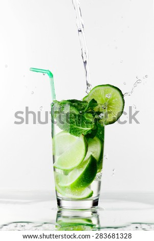 Making mojito cocktail with lime and mint isolated on white background - stock photo