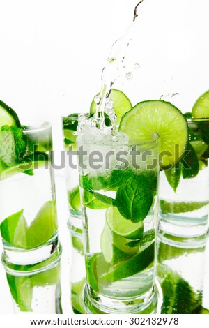 Making mojito cocktails with lime and mint isolated on white background - stock photo