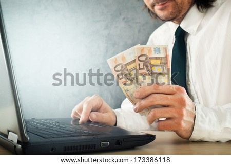 Making money online, businessman with laptop computer is earning money over internet.