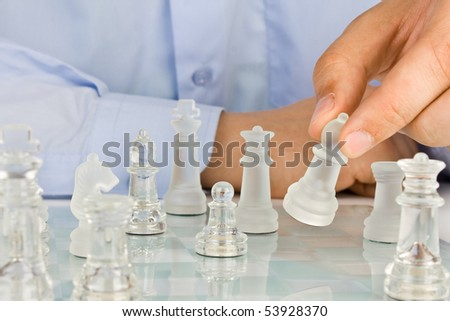 Making move on glass chessboard - stock photo