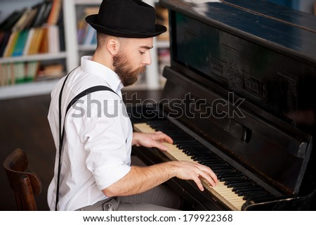 Making music. Profile of a handsome young bearded men playing piano - stock photo