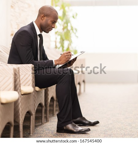 Making notes. Side view of confident young African businessman writing something in his note pad while sitting on the chair  - stock photo