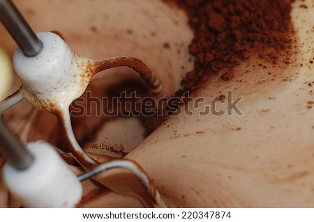 Making of a cream for home-made cakes on a mixer, cooking, whipping eggs and cocoa with electric whisk. - stock photo