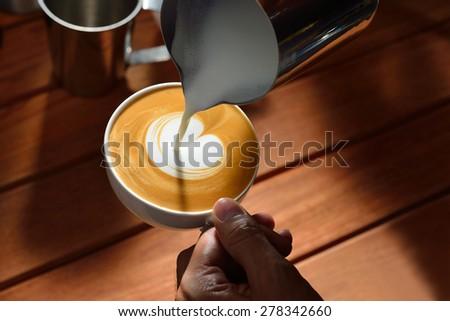 Making of cafe latte art, heart shape - stock photo