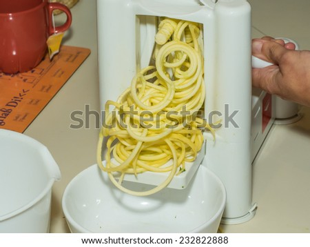 Making of spiral yellow squash spaghetti imitation noodles. - stock photo