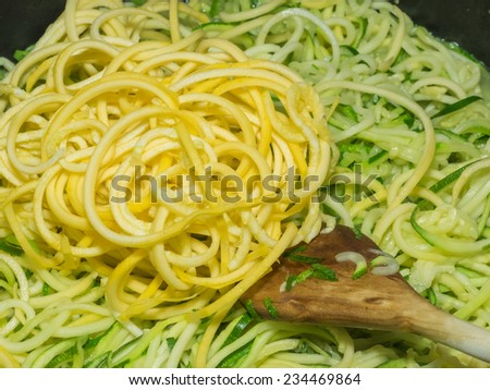 Making of spiral yellow squash spaghetti imitation noodles. - stock photo