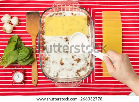 Making of tasty Italian lasagna on a bright background - stock photo