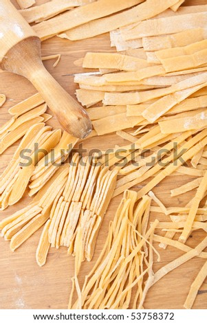 Making Pasta: Homemade Pasta Sheets into Strips - stock photo