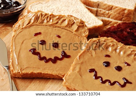 Making peanut butter sandwiches with personality! Fun smiley faces drawn on with jam. Creamy peanut butter with jam on whole grain wheat bread on wood cutting board. Macro with shallow dof. - stock photo